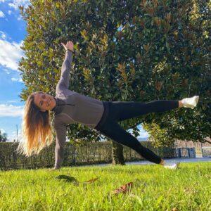 Una chica en un parque, sobre el césped, haciendo una plancha lateral, con un brazo y una pierna estiradas hacia el cielo.