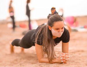 Una chica en la playa haciendo una plancha abdominal clásica, con los antebrazos apoyados en el suelo
