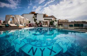 Piscina del hotel NYX Madrid, con sus azulejos de inspiración portuguesa y sus camas balinesas